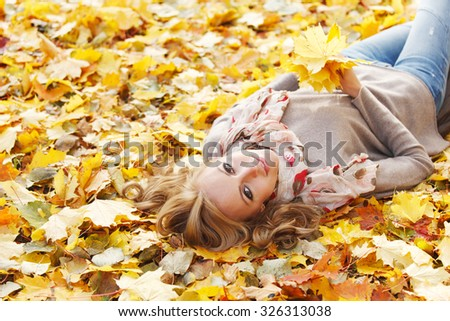 Young woman lies in maple leaves at autumn park