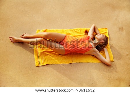 Young woman lies in summer on the beach - stock photo