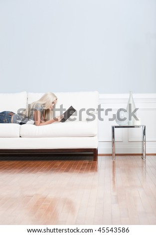 Young woman lies on a white sofa in a checkered top and blue jeans while reading a book. Vertical shot. - stock photo