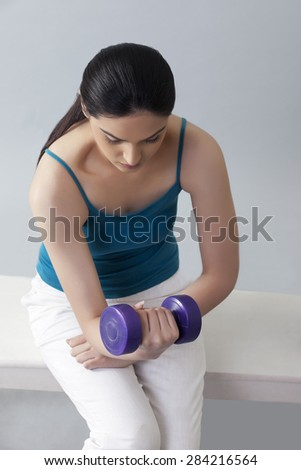 Young woman lifting dumbbells while sitting on bench against gray background