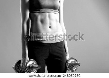 Young woman lifting the dumbbells - stock photo