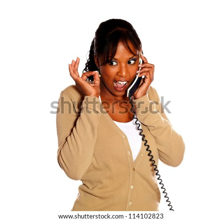 Young woman lifting the fingers up and speaking on phone against white background