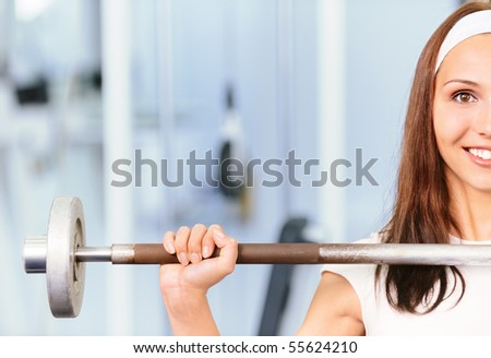 Young woman lifts weight and smiles, against sports hall. - stock photo