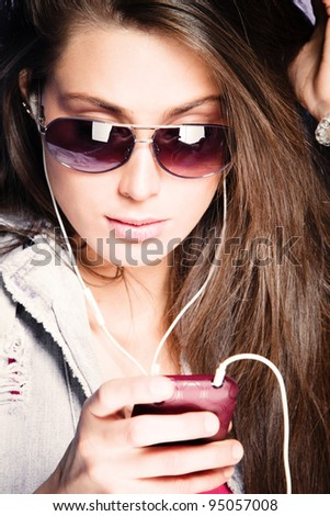 young woman listen music from cell phone with earphones wearing sunglasses, studio shot - stock photo