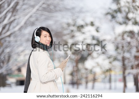 Young woman listen to music with smart phone. - stock photo