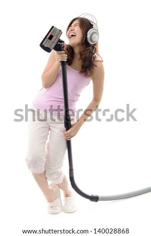 Young woman listening music in headphones and doing housework. Asian female. - stock photo