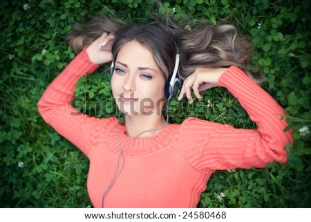 Young woman listening music in park - stock photo