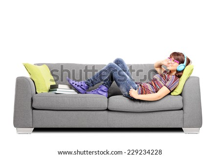 Young woman listening music on headphones and lying on a sofa isolated on white background - stock photo