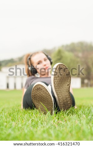 Young woman listening music on headphones while lying cross-legged on grass - stock photo