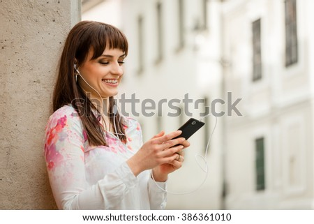 Young woman listening music on phone with headphones in street