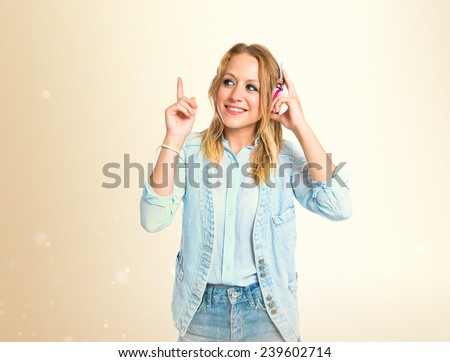 Young woman listening music over ocher background - stock photo