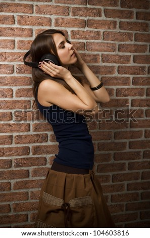 Young woman listening music while leaning on a brick wall with her eyes closed, using wireless headphones
