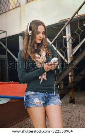 Young woman listening music with cameraphone on an old pier beside the boat. - stock photo
