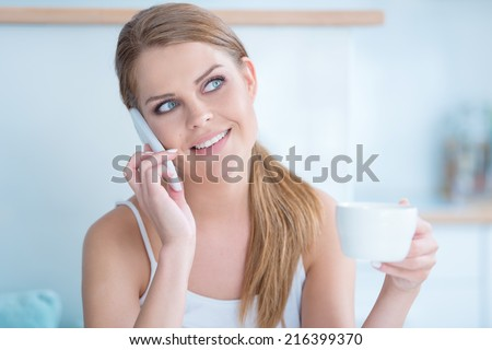Young woman listening to a phone conversation on her mobile phone smiling as she holds a cup of tea or coffee in her hand - stock photo