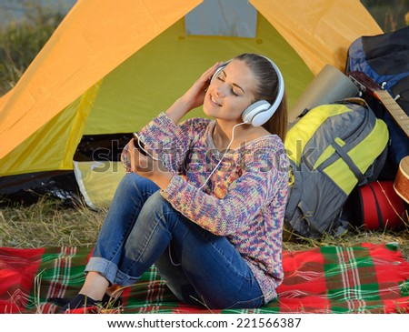 Young woman listening to an mp3 player in a tent