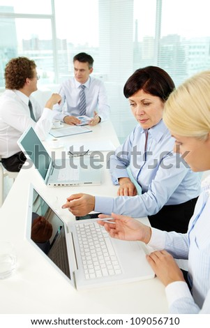 Young woman listening to experienced employee explaining her computer terms - stock photo