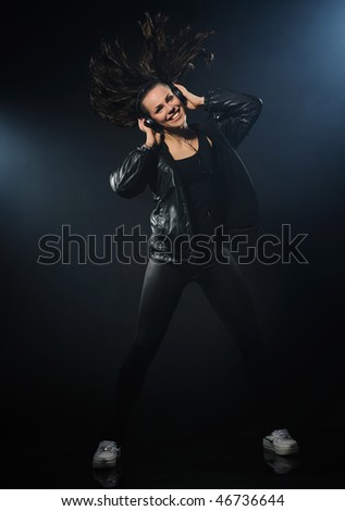Young woman listening to music and dancing on a black background
