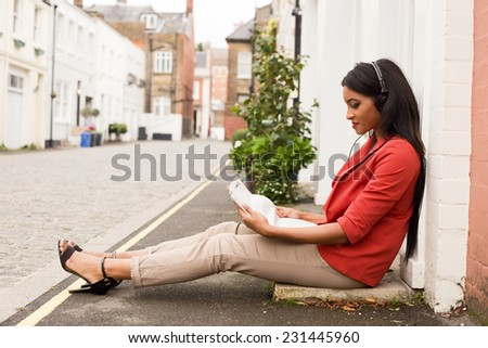 young woman listening to music and reading the newspaper.  - stock photo