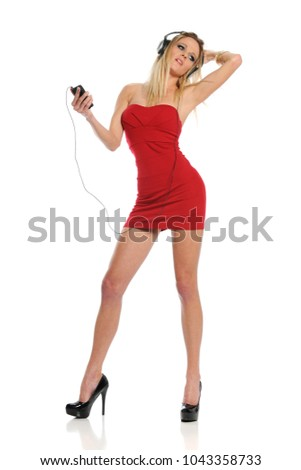 Young woman listening to music and wearind a short red dress