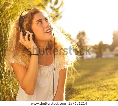 young woman listening to music at park on sunny day - stock photo