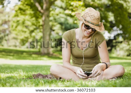 Young woman listening to music in a park - stock photo
