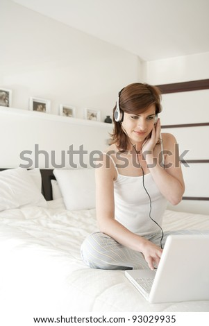 Young woman listening to music in bed, using a laptop computer and headphones. - stock photo