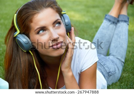 Young woman listening to music in park lying on the grass  - stock photo