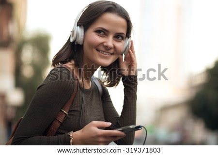Young woman listening to music in the city