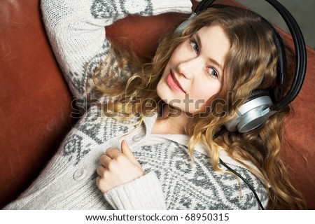 young woman listening to music on the couch and relax while - stock photo