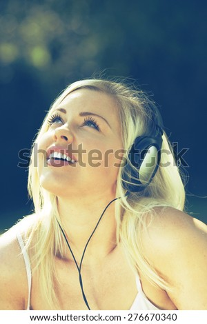 Young woman listening to music or audio book - stock photo