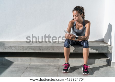 Young woman listening to music with earphones on smart phone app for fitness motivation. Athlete runner in sportswear relaxing sitting getting inspired. Asian mixed race model.