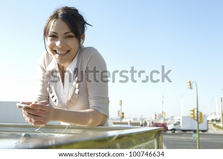 Young woman listening to music with headphones in the city, smiling at camera. - stock photo
