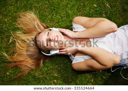 Young woman listening to music with headphones laying on a meadow in summer
