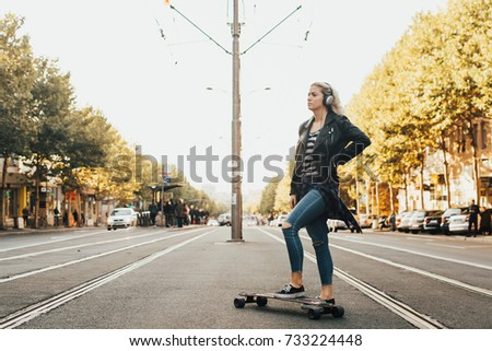 Young woman listening to the music at the street