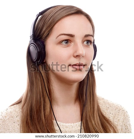 Young woman listening to the music on headphones - stock photo