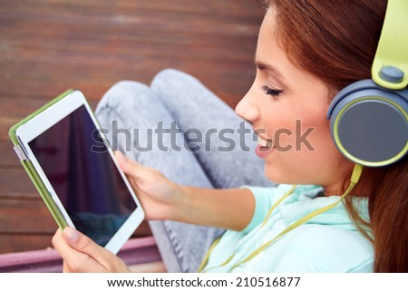 Young woman listens to music on tablet