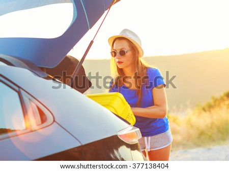 Young woman loading luggage into the back of car parked alongside the road