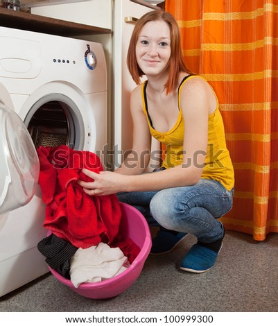 Young woman loading the washing machine in kitchen - stock photo