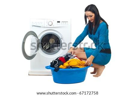 Young woman loading washing machine  isolated on white background - stock photo