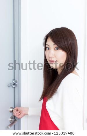 Young woman locking door - stock photo