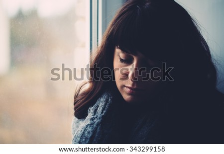 Young woman longs near a window close up photo. - stock photo