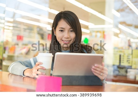 Young woman look at digital tablet in coffee shop