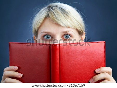 Young  Woman look in wide-eyed of the red book - stock photo