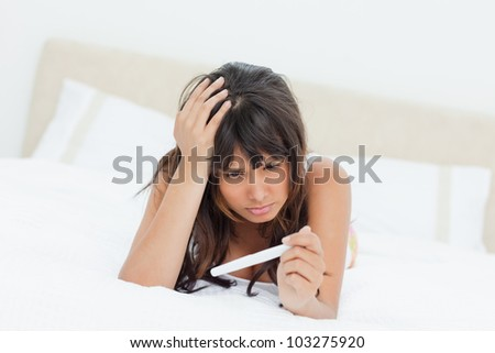 Young woman looking a pregnancy test while lying on a bed - stock photo