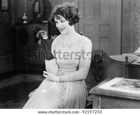 Young woman looking at a monkey hand puppet and smiling - stock photo