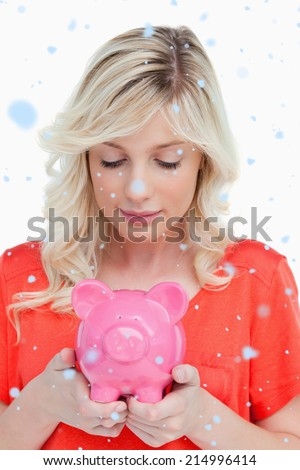 Young woman looking at a piggy bank held by her hands against snow falling - stock photo