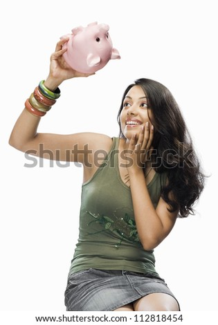 Young woman looking at a piggy bank in shock - stock photo