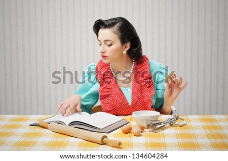Young woman looking at a Recipe for a cake - stock photo