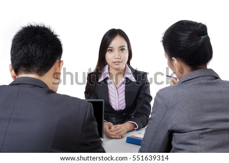Young woman looking at camera and sitting in front of two people in a job interview, isolated on white background
