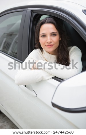 Young woman looking at camera in her car - stock photo
